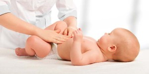 Doctor examines, massaging baby tummy